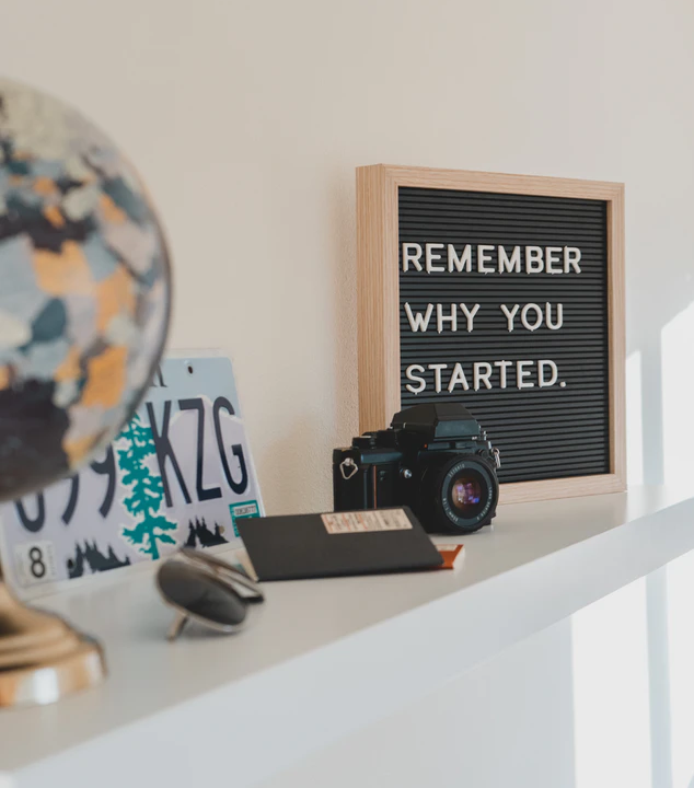 a shelf with a camera, car registration plate and a letterboard that reads 'REMEMBER WHY YOU STARTED.'