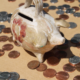 an old ceramic piggy bank surrounded by coins